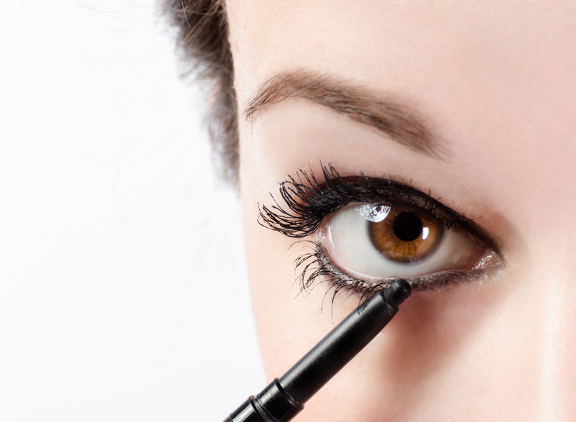 Woman applying make-up with eye pencil